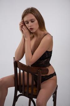 Junge blondine in der schwarzen spitzenunterwäsche, die auf einem hölzernen stuhl sitzt