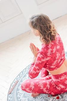Junge blondine in übendem yoga asana namaste des roten ethnischen kostüms im hellen studio