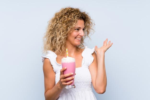 Junge blondine mit dem gelockten haar, das ein erdbeermilchshake mit überraschungsgesichtsausdruck hält
