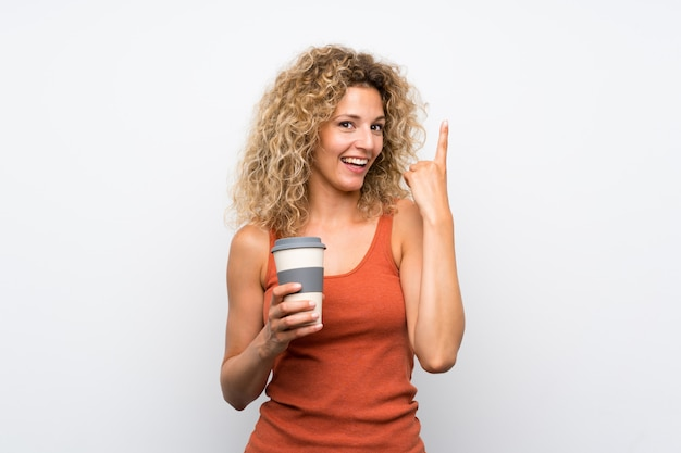 Junge blondine mit dem gelockten haar, das einen mitnehmerkaffee beabsichtigt, die lösung beim anheben eines fingers zu verwirklichen hält