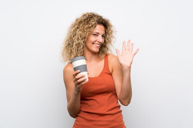 Junge blondine mit dem gelockten haar, das einen mitnehmerkaffee begrüßt mit der hand mit glücklichem ausdruck hält