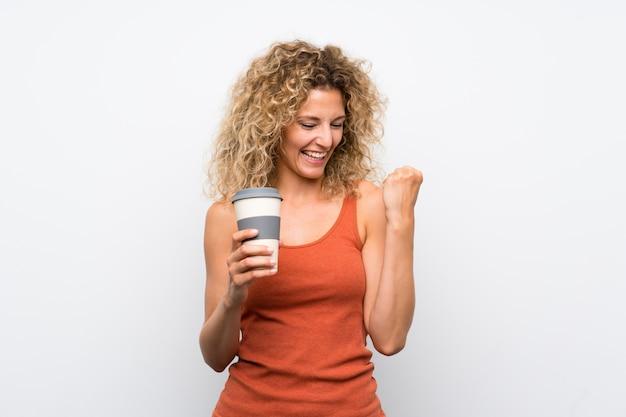 Junge blondine mit dem gelockten haar, das einen mitnehmerkaffee feiert einen sieg hält