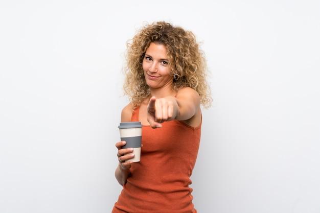 Junge blondine mit dem gelockten haar, das einen mitnehmerkaffee hält, zeigen finger auf sie mit einem überzeugten ausdruck