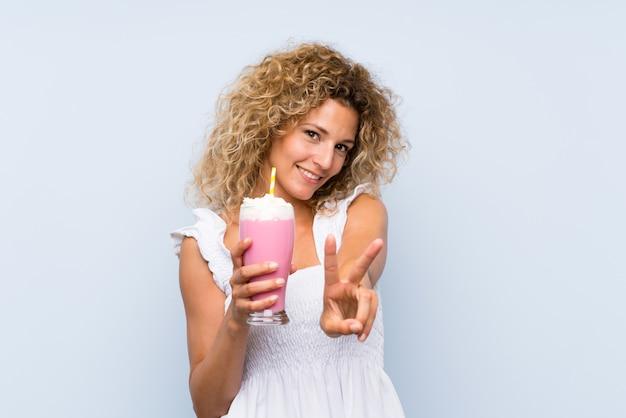 Junge blondine mit dem gelockten haar ein erdbeermilchshake halten, das siegeszeichen lächelt und zeigt