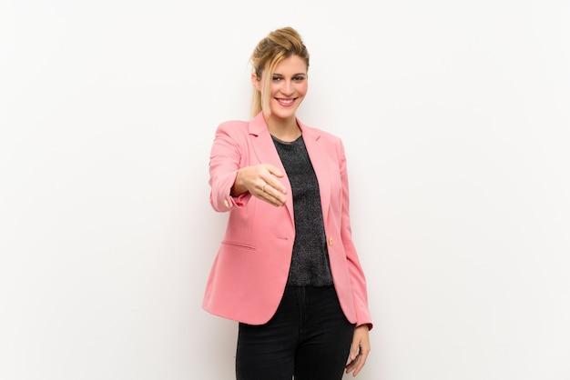Junge blondine mit dem rosa anzug, der hände für das schließen viel rüttelt