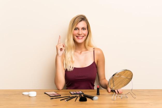 Junge blondine mit kosmetik in einer tabelle zeigend mit dem zeigefinger eine großartige idee
