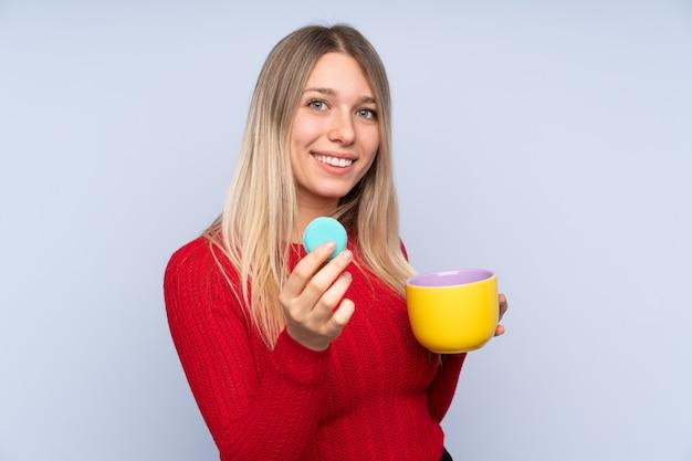 Junge blondine über der lokalisierten blauen wand, die bunte französische macarons und eine schale milch hält