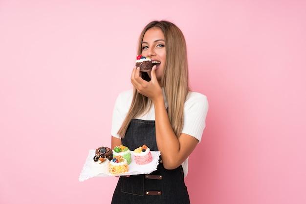 Junge blondine über der lokalisierten rosa wand, die minikuchen hält und es isst