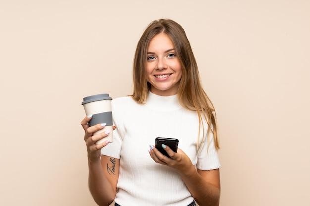 Junge blondine über der lokalisierten wand, die kaffee hält, um und ein mobile wegzunehmen