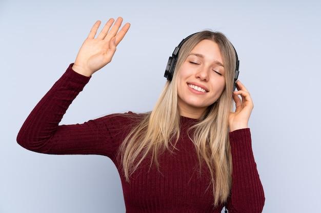 Junge blondine über hörender musik und tanzen der lokalisierten blauen wand