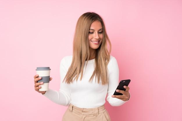Junge blondine über lokalisiertem rosa haltenem kaffee zum mitnehmen und einem mobile