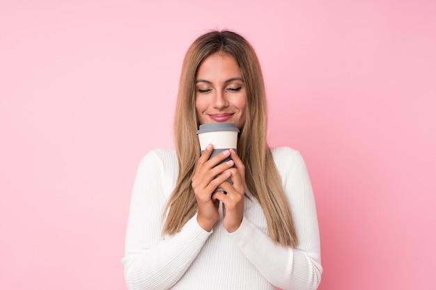 Junge blondine über lokalisiertem rosa haltenem kaffee zum mitnehmen