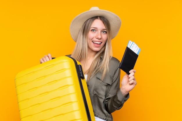 Junge blondine über lokalisierter gelber wand in den ferien mit koffer und pass
