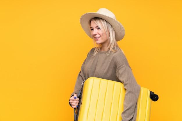 Junge blondine über lokalisierter gelber wand in den ferien mit reisekoffer und einem hut