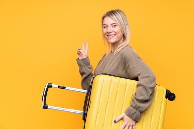 Junge blondine über lokalisierter gelber wand in den ferien mit reisekoffer und sieggeste machend