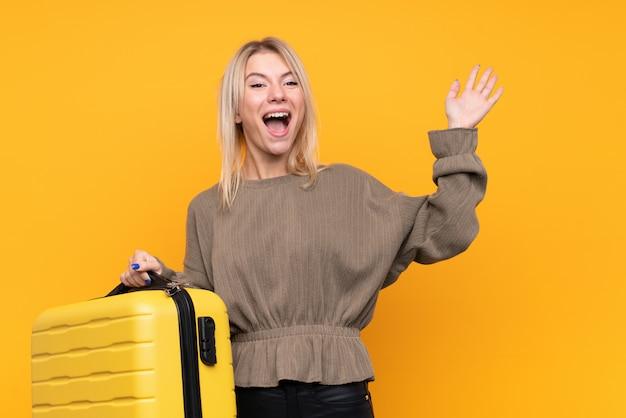 Junge blondine über lokalisierter gelber wand in den ferien mit reisekoffer und überrascht