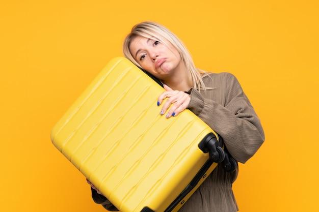 Junge blondine über lokalisierter gelber wand in den ferien mit reisekoffer und unglücklich