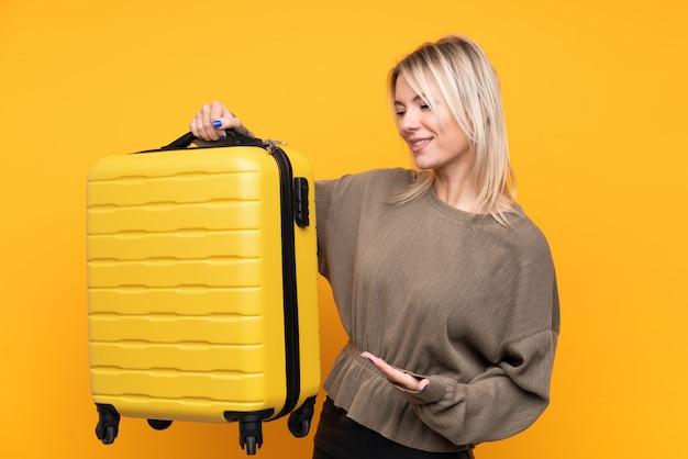 Junge blondine über lokalisierter gelber wand in den ferien mit reisekoffer