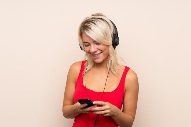 Junge blondine über lokalisierter wand unter verwendung des mobiles mit kopfhörern