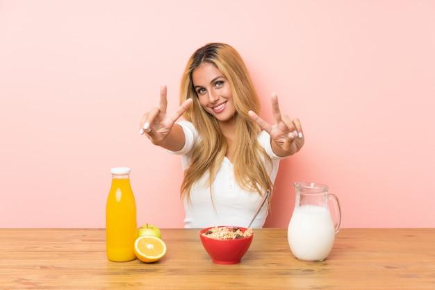 Junge blondine, welche die frühstücksmilch lächelt und siegeszeichen zeigt frühstücken