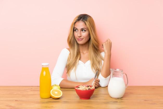 Junge blondine, welche die frühstücksmilch steht und zur seite schaut frühstücken