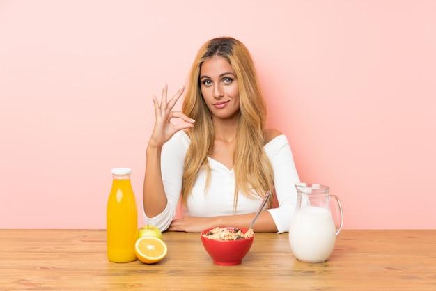 Junge blondine, welche die frühstücksmilch zeigt ein okayzeichen mit den fingern essen