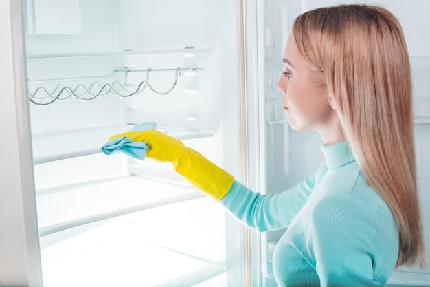 Junge blondine zu hause in der nähe des kühlschranks