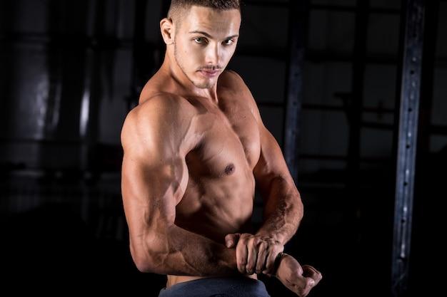 Junge bodybuilder mit starken bizeps