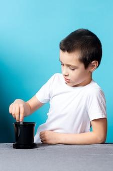 Junge bohrt mit einem reagenzglas löcher in den boden, um einen samen zu pflanzen und eine zimmerpflanze auf dem tisch zu züchten