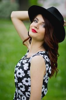 Junge bosnische frau mit rotem lippenstift und hut lächelnd