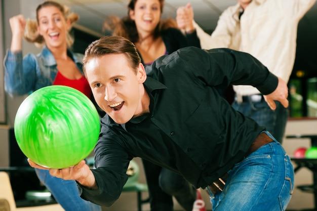 Junge bowling mit freunden