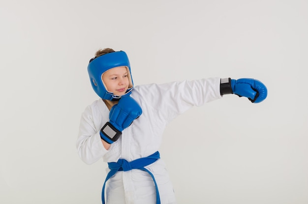 Junge boxer in einer weißen uniform und mit helm und handschuhen übt schläge auf eine weiße wand
