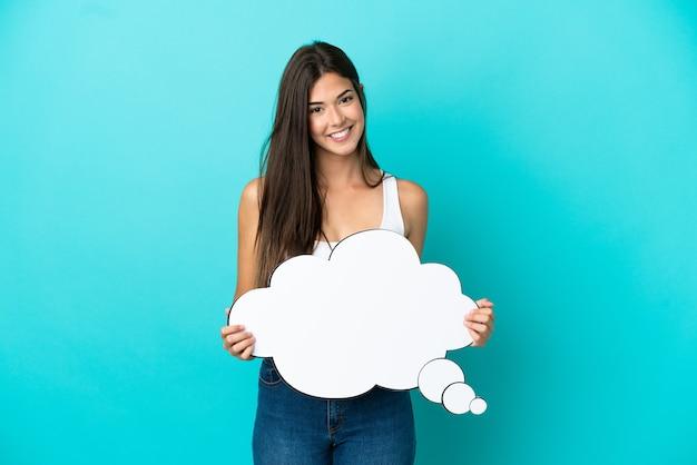 Junge brasilianerin isoliert auf blauem hintergrund mit einer denkenden sprechblase