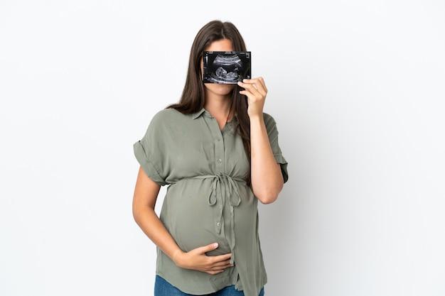 Junge brasilianerin isoliert auf weißem hintergrund schwanger und hält einen ultraschall