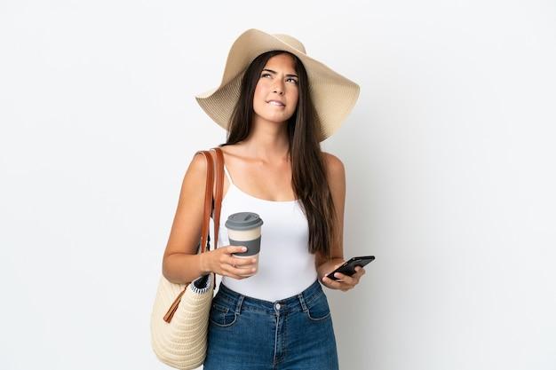 Junge brasilianerin mit pamela, die eine strandtasche isoliert auf weißem hintergrund hält und kaffee zum mitnehmen und ein handy hält, während sie etwas denkt