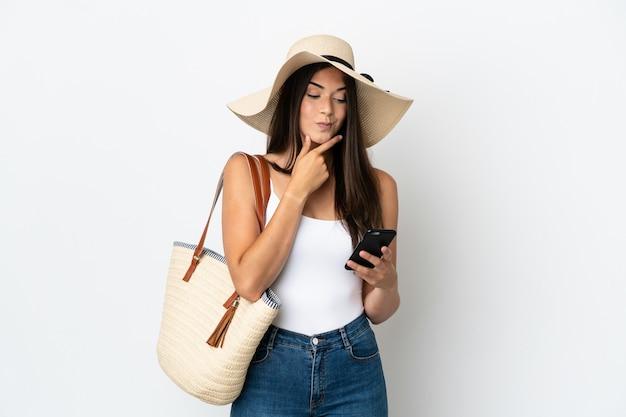 Junge brasilianerin mit pamela hält eine strandtasche isoliert auf weißem hintergrund denkt und sendet eine nachricht