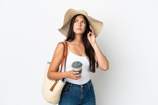 Junge brasilianerin mit pamela hält eine strandtasche isoliert auf weißem hintergrund mit kaffee zum mitnehmen und einem handy