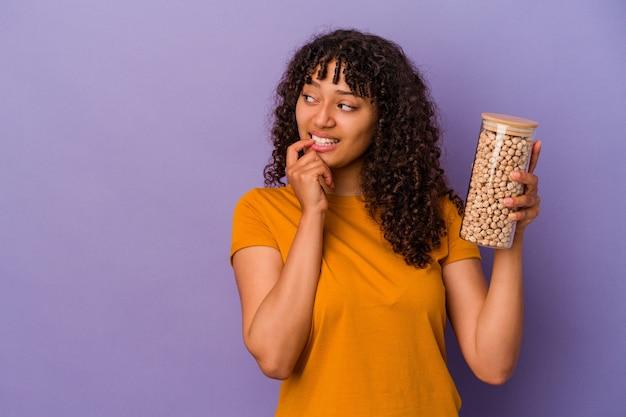 Junge brasilianische frau, die eine kichererbsenflasche einzeln auf violettem hintergrund hält, entspannte sich beim nachdenken über etwas, das einen kopienraum betrachtet.