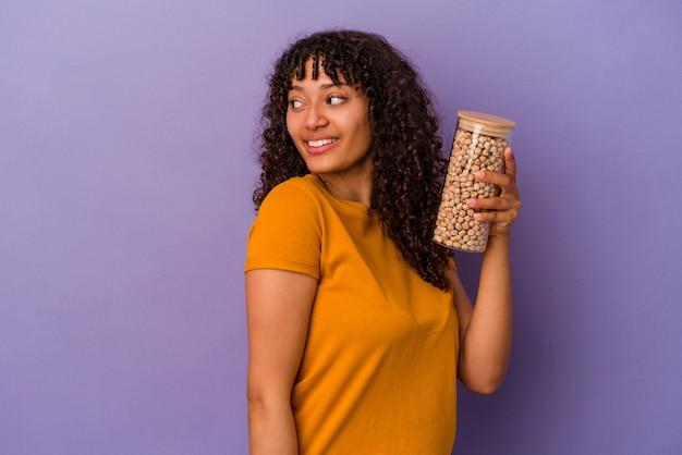 Junge brasilianische frau, die eine kichererbsenflasche einzeln auf violettem hintergrund hält, sieht beiseite lächelnd, fröhlich und angenehm aus.