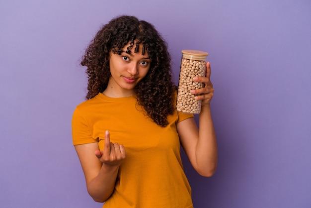 Junge brasilianische frau, die eine kichererbsenflasche einzeln auf violettem hintergrund hält und mit dem finger auf sie zeigt, als ob sie einladen würde, näher zu kommen.