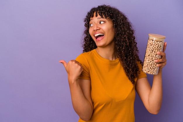 Junge brasilianische frau, die eine kichererbsenflasche einzeln auf violettem hintergrund hält, zeigt mit dem daumenfinger weg, lacht und sorglos.