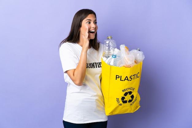 Junge brasilianische frau, die eine tasche voller plastikflaschen hält, um auf purpurgeschreiem schreien mit dem mund weit offen zur seite zu recyceln