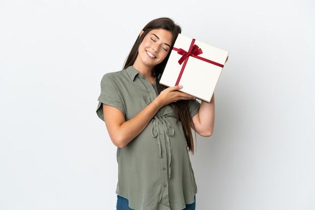 Junge brasilianische frau isoliert auf weißem hintergrund schwanger und hält ein geschenk