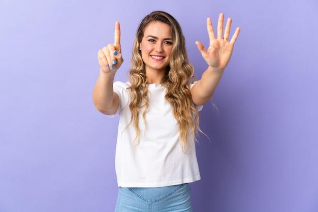 Junge brasilianische frau lokalisiert auf purpur, das sechs mit den fingern zählt