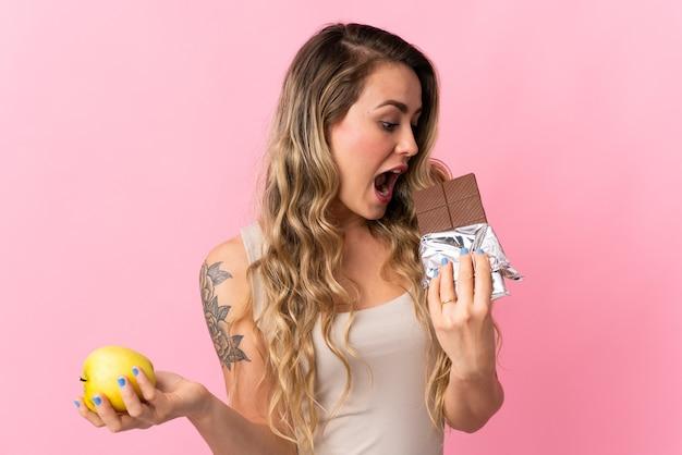Junge brasilianische frau lokalisiert auf rosa, die eine schokoladentafel in einer hand und einen apfel in der anderen nimmt