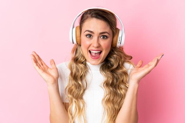 Junge brasilianische frau lokalisiert auf rosa überraschte und hörende musik