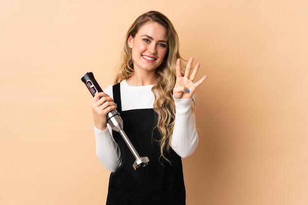 Junge brasilianische frau mit handmixer lokalisiert auf beige wand glücklich und zählt vier mit den fingern