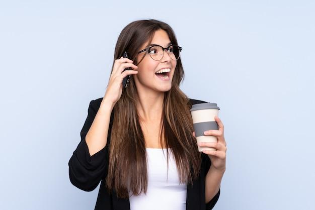 Junge brasilianische geschäftsfrau, die kaffee hält, um mit mobile wegzunehmen und zu sprechen