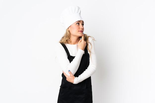 Junge brasilianische kochfrau lokalisiert auf weiß, das zweifel beim aufblicken hat