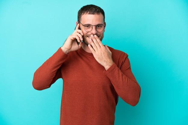 Junge brasilianische mann mit handy isoliert auf blauem hintergrund glücklich und lächelnd den mund mit der hand bedeckend